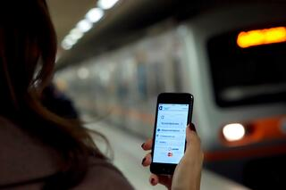 mobile ticketing with metro train in background